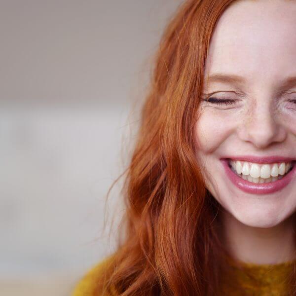 lachende frau mit roten haaren und sommersprossen